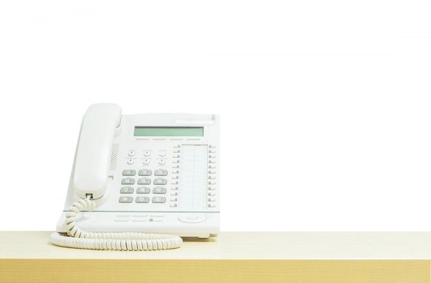 Closeup white phone , office phone on blurred wooden desk in the meeting room u