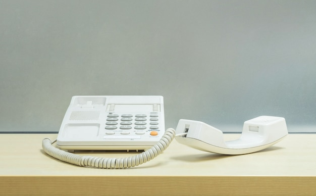 Closeup white phone , office phone on blurred wooden desk