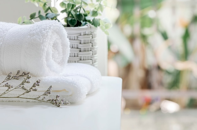 Closeup white towels and houseplant on white table near the window in modern house, copy space.