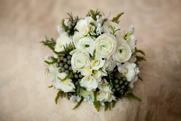 Closeup of white wedding bouquet lying on blanket
