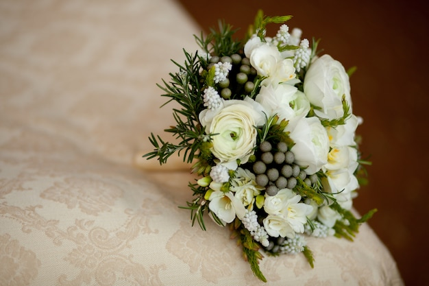 Closeup of white wedding bouquet lying on blanket