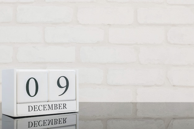 Closeup white wooden calendar with black 9 december word on black glass table and white brick wall