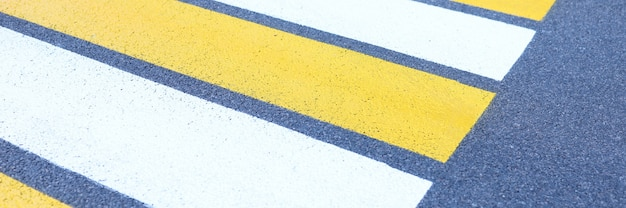 Closeup of white and yellow stripes on gray asphalt background
