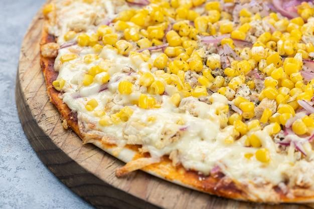 Primo piano di un'intera pizza deliziosa con formaggio fuso, mais e cipolle su una tavola