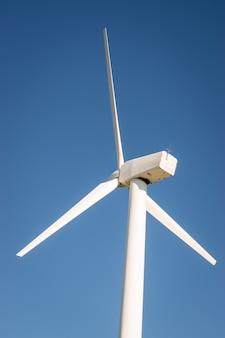 Closeup of a wind turbine on the background blue sky