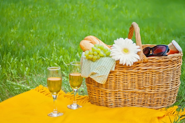 Closeup of wine glasses on the yellow cover, picnic basket with food and flower on the green grass
