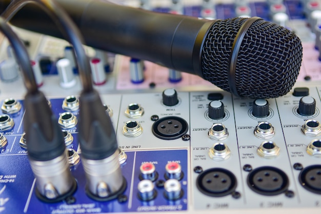 Closeup wireless microphone on audio mixer background.