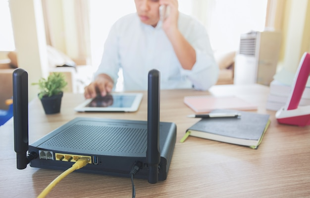 Closeup of a wireless router and a man using smartphone on living room at home ofiice, equipment for  working from home,