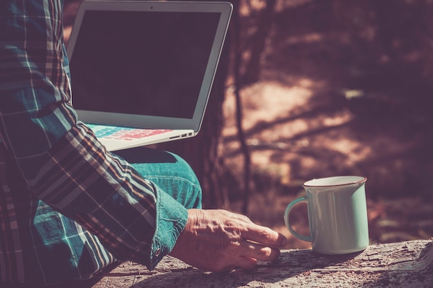 Closeup with old aged hand taking a cup of coffee while use and check a laptop internet connected in the forest. people love travel and discover the world helped from technology and modern related dev