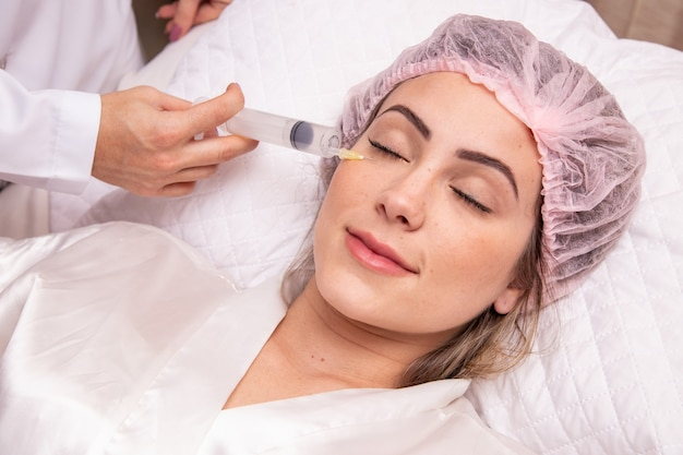 Closeup of woman applying ozone to her face for cosmetic treatment.