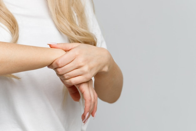 Closeup of woman arms holding her painful wrist caused by prolonged work on the computer, laptop. carpal tunnel syndrome, arthritis, neurological disease