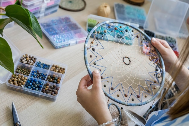 Closeup woman artist creating handmade accessory dreamcatcher use colorful beads amulet for luck
