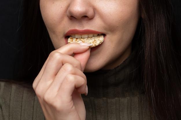 Closeup of a woman biting a cracker under the lights