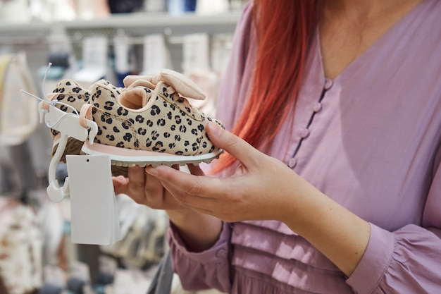 Closeup woman buys baby shoes for a child