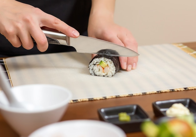 Closeup of woman chef cutting japanese sushi rolls with rice, avocado and shrimps on nori seaweed sheet