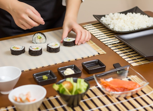 Closeup of woman chef putting japanese sushi rolls with rice, avocado and shrimps on nori seaweed sheet