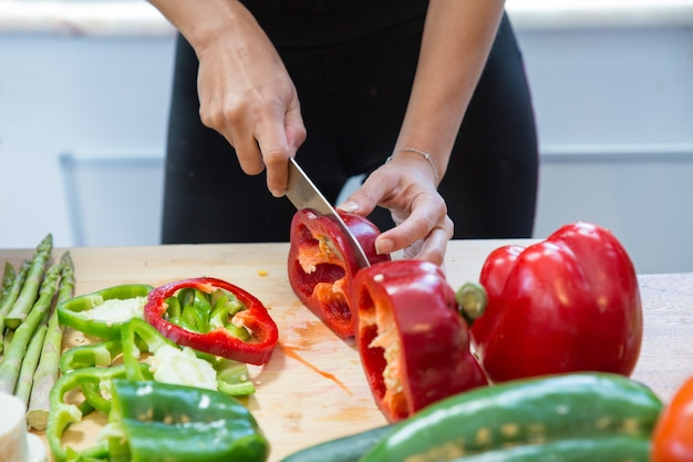 Closeup of woman cutting fresh sweet pepper