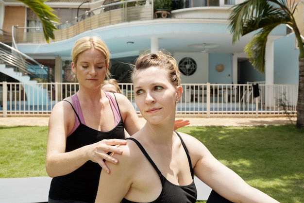 Closeup of woman doing yoga with personal trainor in front yard outdoors with large mansion behind