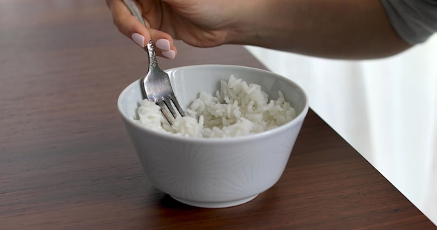Closeup of woman eating rice from bowl