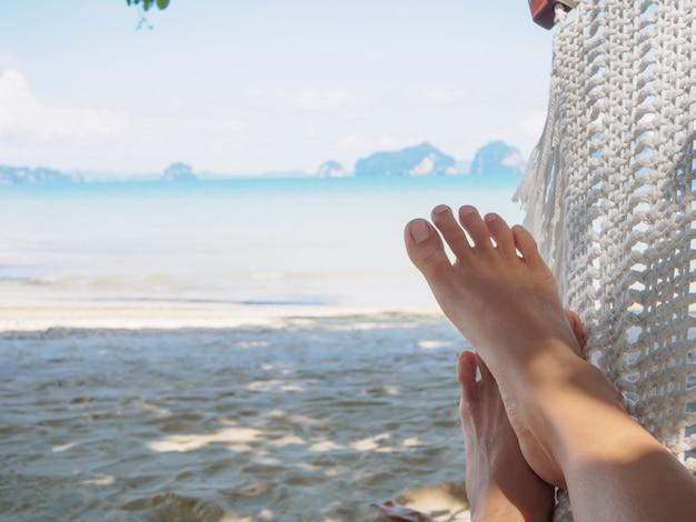 Closeup woman feet lying on hammock with trees and beautiful sea