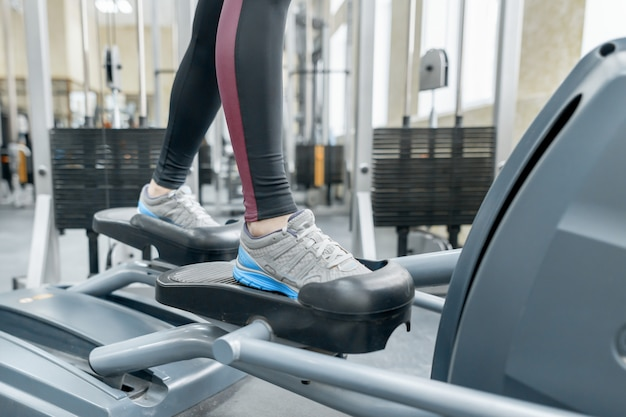 Closeup of woman feet running on treadmill in gym