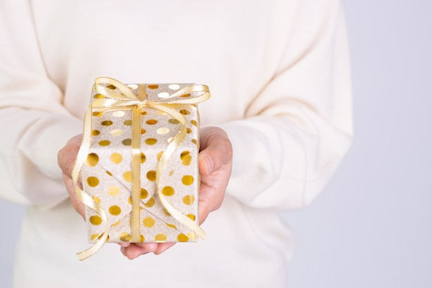 Closeup woman hand deliveries a gold package gift  box with gold ribbon. birthday, christmas, boxing day concept.