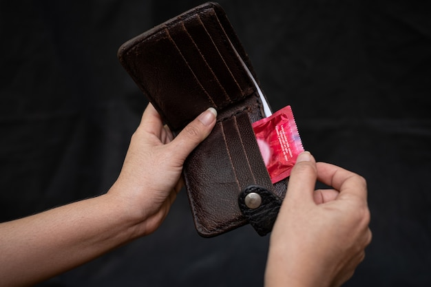 赤いコンドームと黒革の財布を持つクローズアップ女性手
