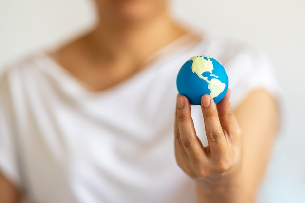 Closeup of woman hand holding and show the mini world ball.