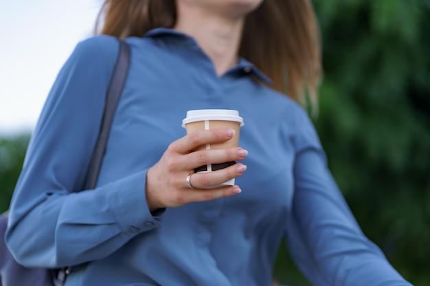 クローズアップ女性は街でテイクアウトのコーヒーを飲みながら動きます。屋外の温かい飲み物と紙コップを保持している肖像画のブロンドの女の子。