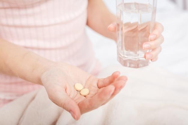頭痛の治療のための薬の錠剤と水のガラスとクローズアップの女性の手