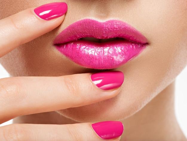 唇の近くにピンクの爪を持つクローズアップの女性の手。ピンクのマニキュアと指の爪