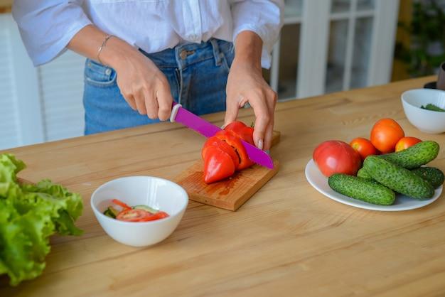 Крупным планом женщина руки нарезая огурцы овощи ножом