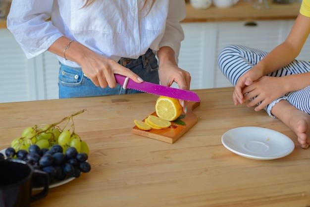 Крупным планом женские руки режут лимон острым ножом на кухне