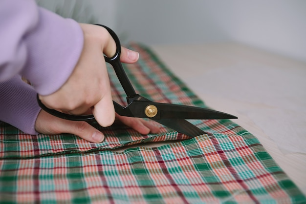 Closeup of woman hands holding scissors and cutting plaid fabric for sewing clothes
