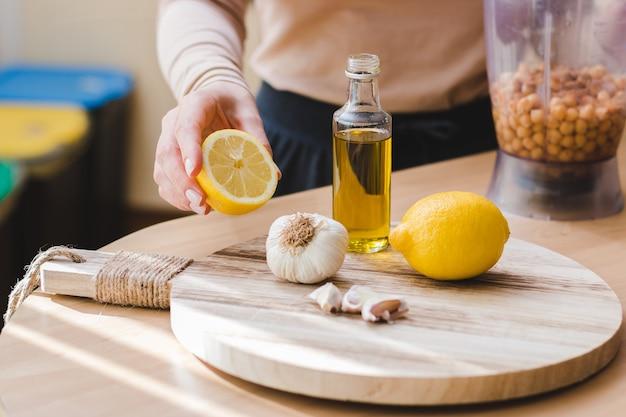 自然な菜食主義の食糧自家製ひよこ豆のフムスのレシピを準備するクローズアップの女性の手
