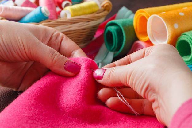Closeup of woman hands sewing pink hamdmade toy