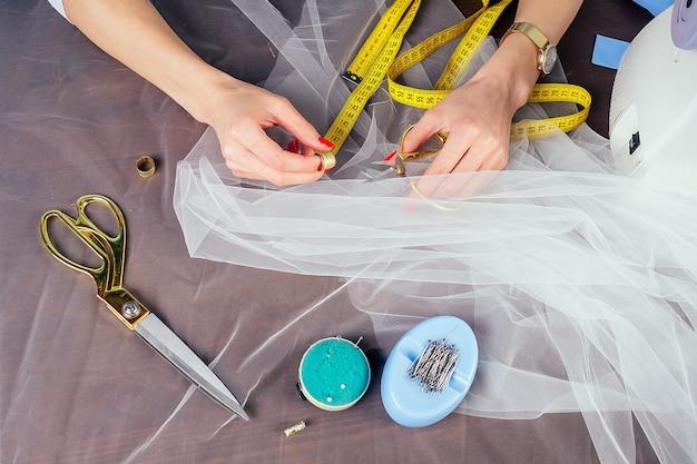 クローズアップの女性は、スタジオの青い背景にミシンで縫う仕立ての結婚式の洋裁の針子を手します。ウェディングドレスの新しいコレクションを作成するというコンセプト。