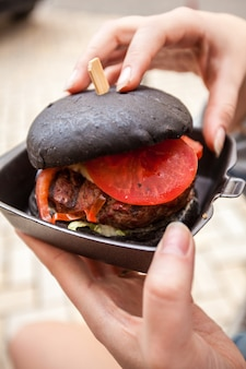 Closeup of woman holding black burger with marbled beef
