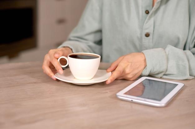 Женщина крупным планом, держащая чашку кофе и белую таблетку на столе