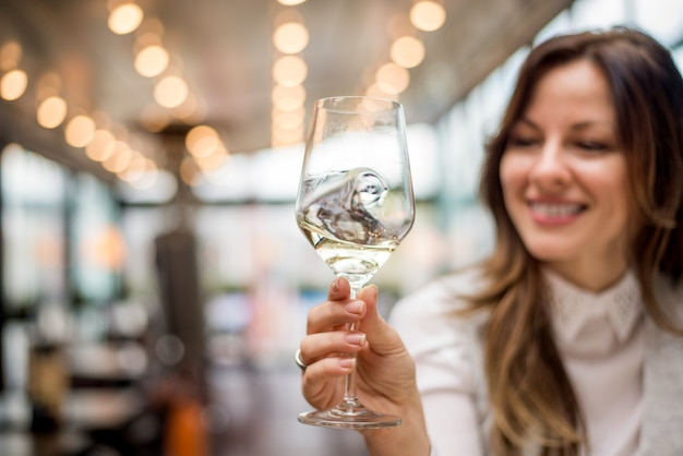 Closeup of woman holding glass of wine in cafe restaurant.