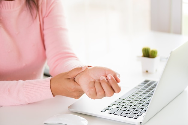 Closeup woman holding her wrist pain from using computer. office syndrome