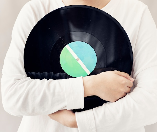 Closeup of woman holding music vinyl record disc