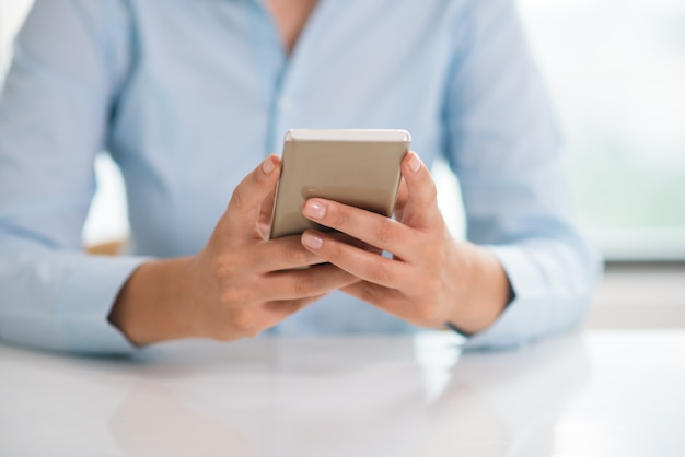 Closeup of woman holding and using smartphone at table