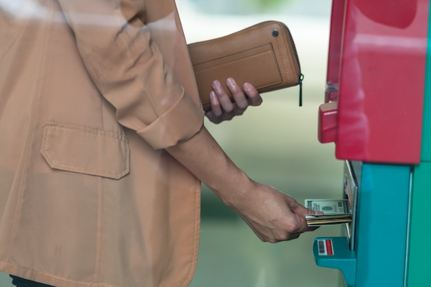 Closeup woman holding the wallet and withdrawing the cash via atm