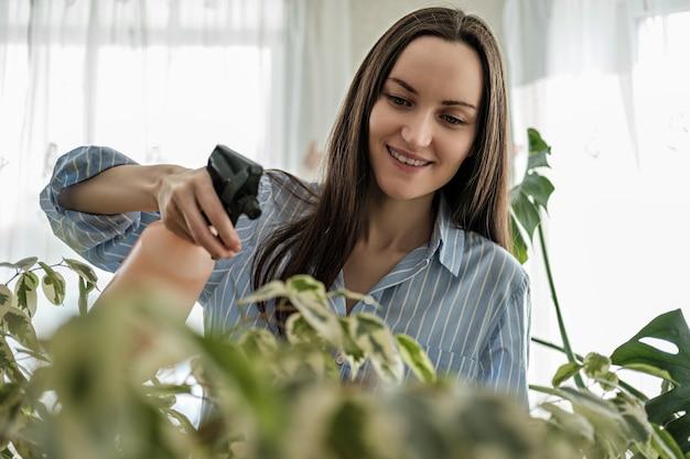青いシャツのクローズアップの女性は植物、植物ケアの概念をスプレーします