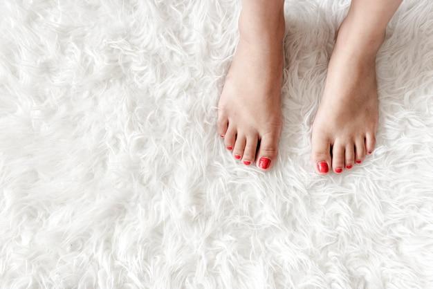 Closeup of woman legs on white fluffy carpet