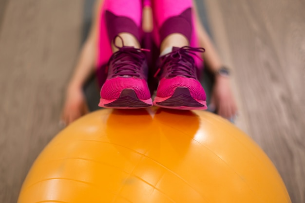 Closeup woman legs on yellow fit sportball in gym. sport and fitness lifestyle concept