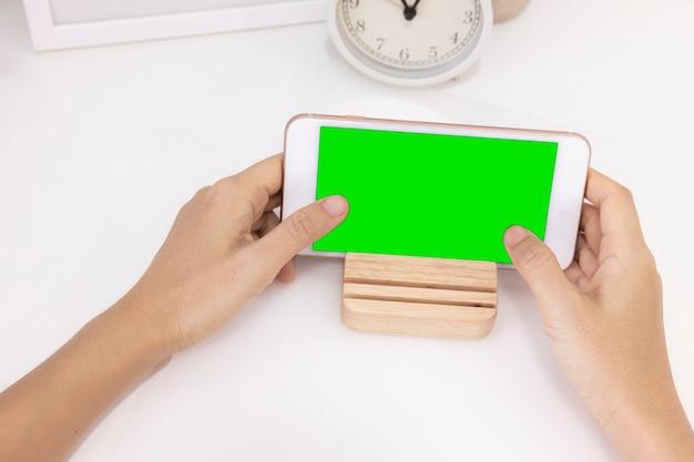 디지털 스마트폰 녹색 화면이 분리된 왼손 사용 손가락 터치의 근접 촬영 여성