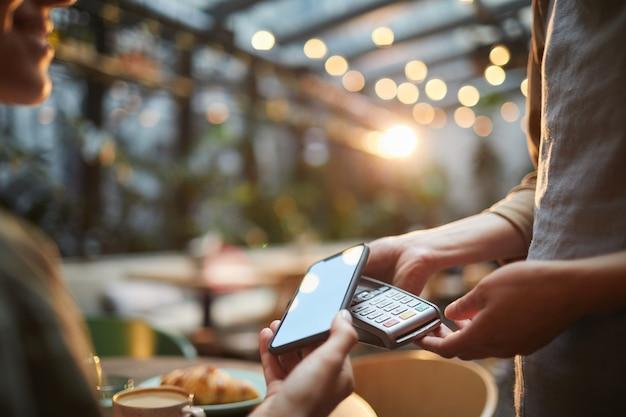 Крупным планом женщина платит через смартфон в кафе