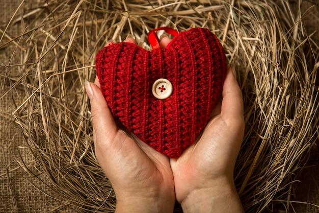 Крупным планом женщина защищает красное вязаное сердце